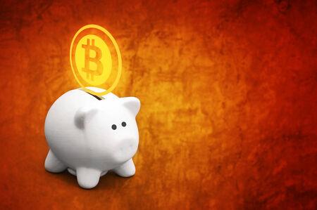 Saving bitcoins in piggy coin bank, conceptual image photo