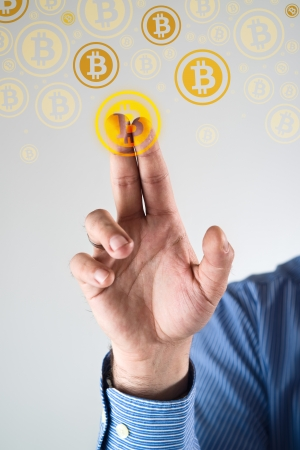 Collecting bitcoins, businessman pressing bitcoin icon  Conceptual image  photo