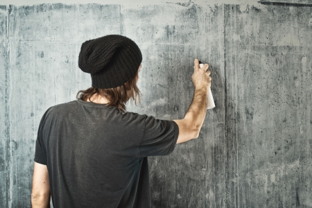 Graffiti artist in black clothes spraying the wall