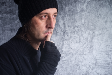 introspective: Looking into the future  Casual man with sad eyes making future plans  Stock Photo