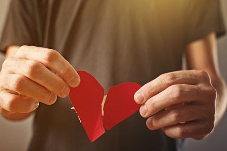 corazon roto: Broken hearted man día de San Valentín concepto Hombre sosteniendo el corazón roto en las manos Foto de archivo
