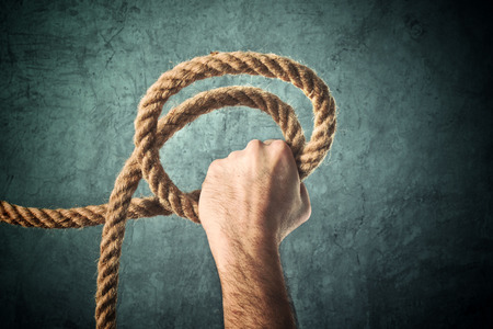 salvation: Male hand holding rope for salvation against grunge background