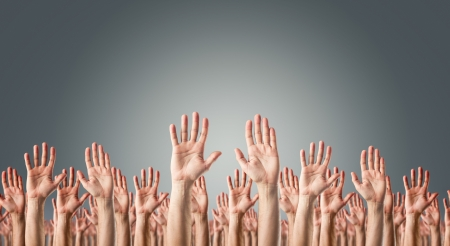 Hands raised in the air over gray background  Surrender or voting concept