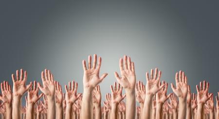 manos levantadas: Las manos levantadas en el aire sobre gris Surrender fondo o el concepto de votación Foto de archivo
