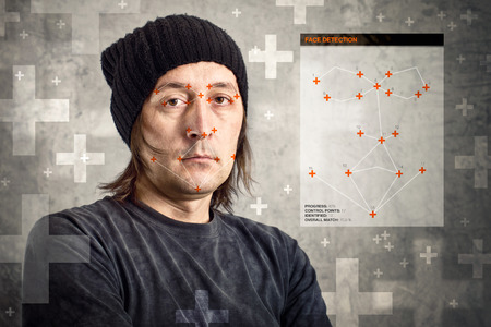 recognizing: Face detection software recognizing a face of man with black cap