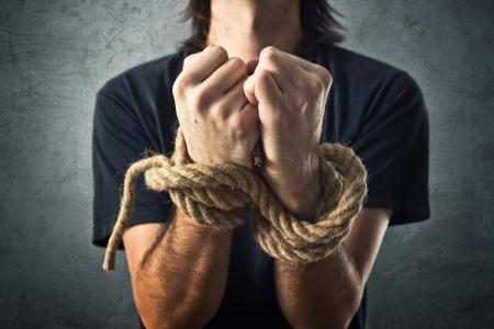 Mannelijke handen vastgebonden met een touw. Gevangenschap concept.