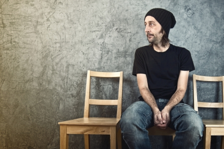 Casual man sitting on wooden chair and waiting. On hold concept.