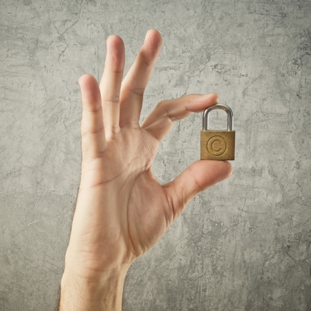 copyright symbol: Hand holding padlock with Copyright symbol. Security and insurance concept. Stock Photo