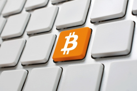 Bitcoin symbol on white computer keyboard. Internet currency concept.