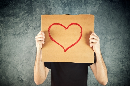 Man holding cardboard paper with heart shape drawing as Valentines day conceptual image. photo