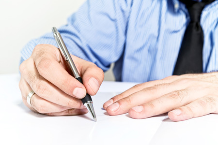 Businessman signing contract. Business man in blue shirt is signing agreement document. Reklamní fotografie