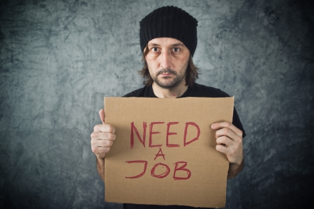 hard times: Man holding cardboard paper with Need a Job message. Job seeking, unemployment issues.