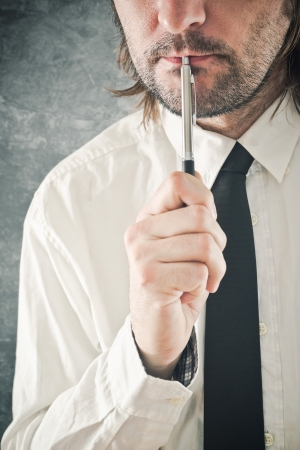 assume: Businessman thinking with pencil in his mouth. Portrait of thoughtful business person. Stock Photo