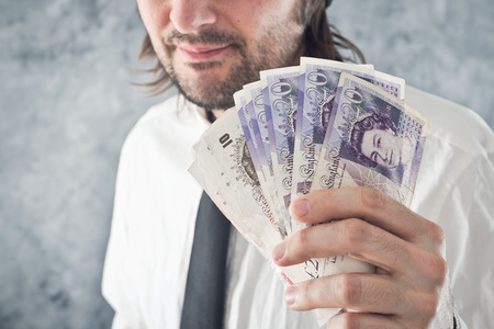 british money: Businessman holding British pounds money. Paying with British currency.