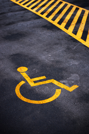 disabled parking sign: Disabled person parking place permit mark, traffic symbol on the asphalt road Stock Photo