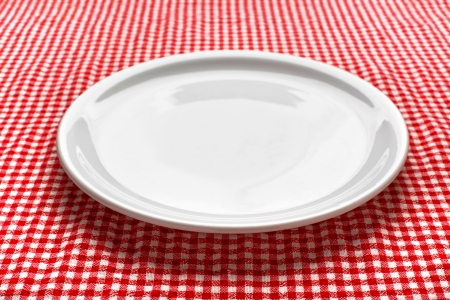 checker plate: Empty white plate on kitchen table covered with checkered tablecloth  Stock Photo