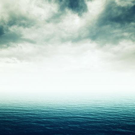 重い嵐雲と青い海、不確かな将来のイメージ 写真素材