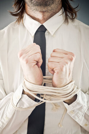 Businessman with hands tied in ropes. Business problems and difficulties, obstructions and limits in work. photo