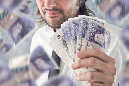 sterlina: Businessman holding britannica sterline di denaro, le banconote che cadono dal cielo pagamento con valuta britannica