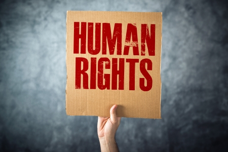 human rights: Man holding cardboard paper with HUMAN RIGHTS title, conceptual image