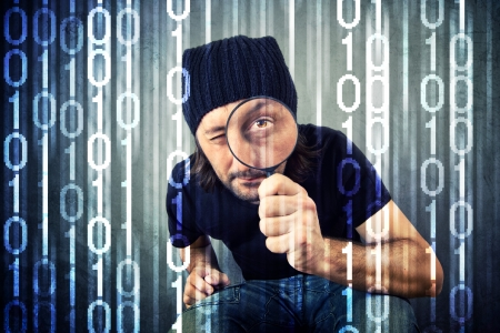 Man looking through magnifying glass and inspecting binary code photo