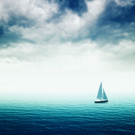 surface tension: Sailing boat on Blue sea with heavy storm clouds, conceptual image of uncertain future