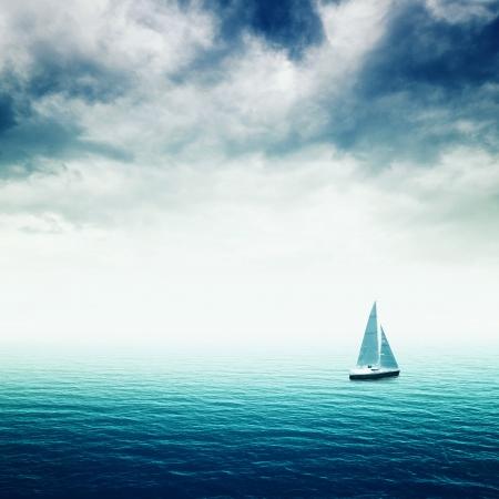 Zeilboot op de blauwe zee met zware onweerswolken, conceptueel beeld van onzekere toekomst