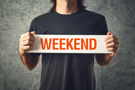 weekend break: Man holding bboard with WEEKEND title. Interlude concept. Stock Photo
