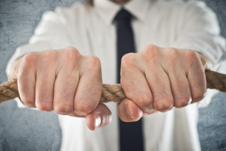 Businessman holding tight to a rope. Concept of business problems, difficult business situation. Stock Photo