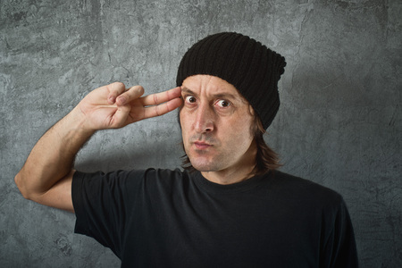 suicidal: Casual man pointing his fingers to his head as if he is about to shoot himself. Suicidal tendencies or threating someone. Stock Photo