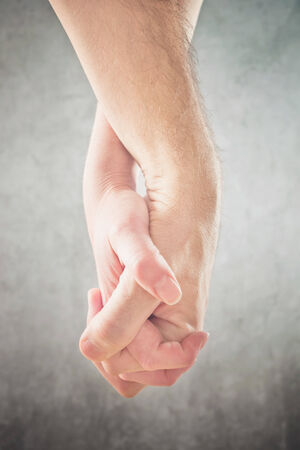 couple holding hands: Couple holding hands. Man and woman holding hands, cose up.