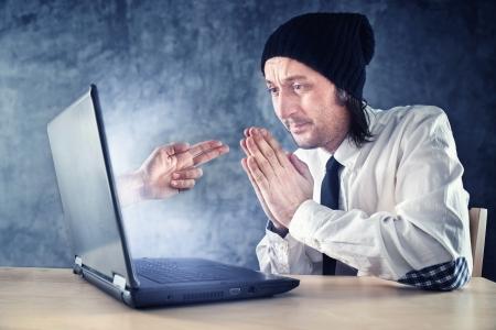 beroofd: Online diefstal. Zakenman wordt bestolen via internet tijdens het werken op laptop computer.