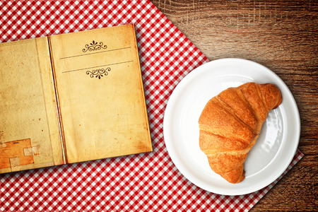 copys pace: Croisant recipe. Croissant on a plate and old open recipe book with copys pace for your text.