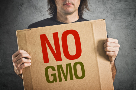 opponents: No GMO  Man holding banner with Anti GMO message  Stock Photo