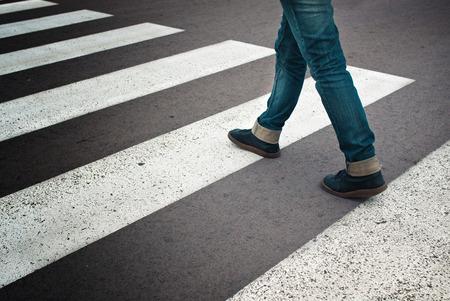 Benen van jonge vrouw in jeans en leren laarzen oversteken straat op zebra markering