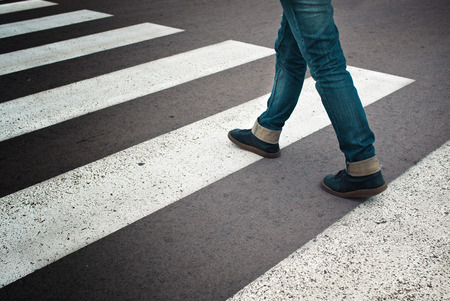 Legs of young woman in jeans and leather boots crossing street on zebra marking Stock Photo