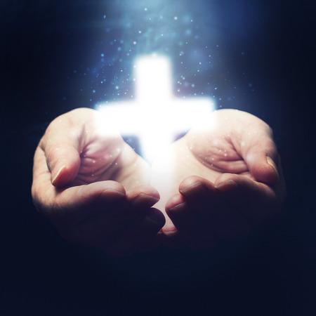 Jezus: Otwarte ręce trzyma krzyż, symbol wiary chrześcijańskiej