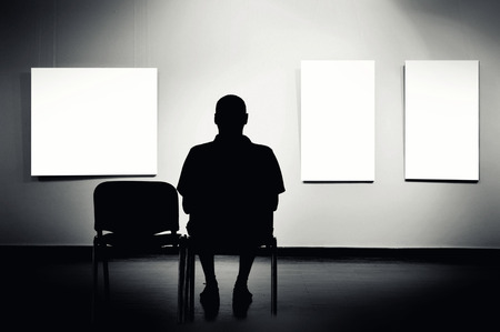 art thinking: Man sitting in art gallery, looking at art displayed on walls.