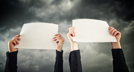 blank papers: Two women holding blank papers above their heads