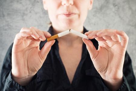 Hábitos saludables: Mujer deja de fumar y cigarrillos de ruptura en medio