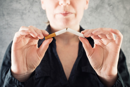 Woman quits smoking and breaking cigarette in half Imagens