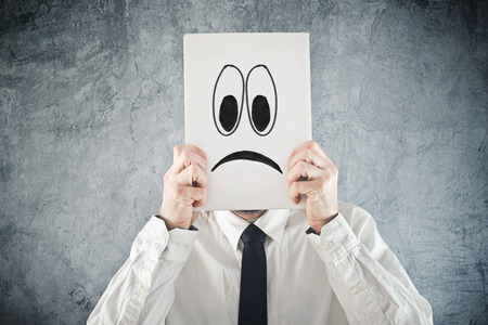 pathetic: Businessman holding paper with sad face in front of his head Stock Photo