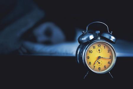 sono: Homem novo que dorme na cama com um despertador