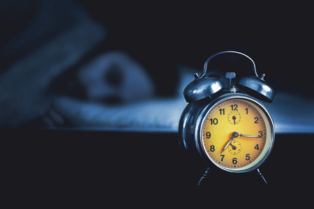 time  clock: Young man sleeping in the bed with an alarm clock Stock Photo