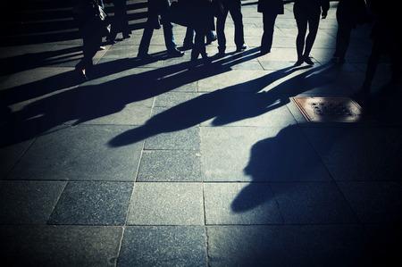 Schaduwen van de mensen op de stoep Mensen lopen de straat
