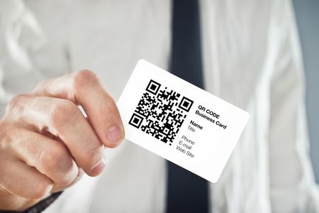 Businessman holding QR code business card with personal data  Modern technology concept