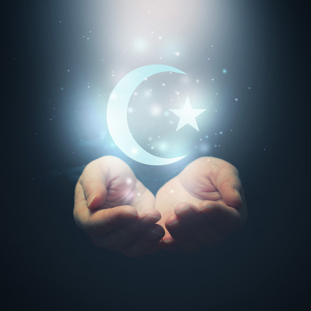 Female hands opening to light and Halh moon and star, symbol of islam religion
