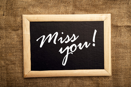 Miss you note on black message board