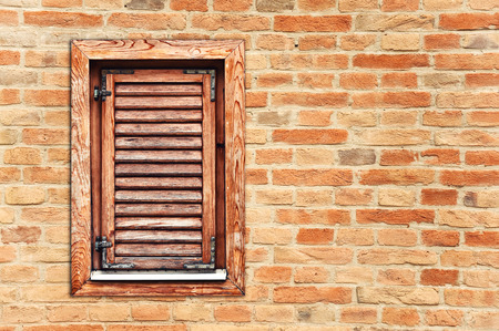 Italyan style wooden window with closed shutter blinds on brick wall photo