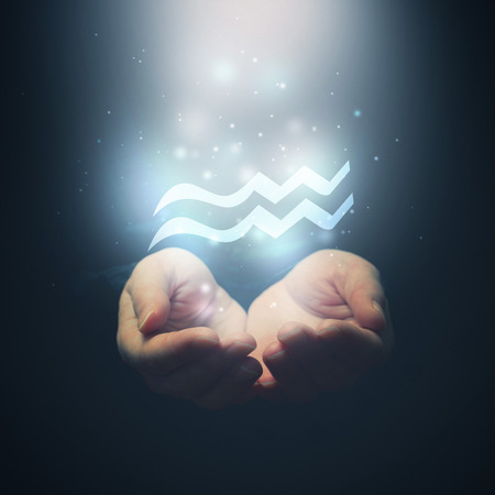 aquarius: Female hands opening to light and holding zodiac sign for Aquarius  Horoscope symbols  Selective focus  Stock Photo